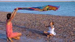 Girl with her mother played on the beach Stock Footage