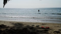 Two pairs of slippers on beach sand and woman in ocean in Island - stock footage