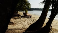 Woman sitting on tropical beach bed and reading book in Thailand Island Stock Footage