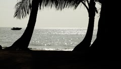 Boat passing by exotic beautiful tropical beach silhouetted in Island Stock Footage