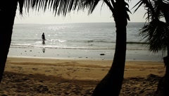Woman getting into ocean in exotic beautiful tropical beach in island Stock Footage