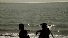 Beautiful sparkling surface of ocean and two men walking on tropical beach  Stock Footage