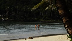 Young couple holding hands and walking on exotic tropical beach shore in island  Stock Footage
