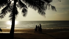 Family of five walking on tropical beach shore silhouetted in Island at sunset  Stock Footage