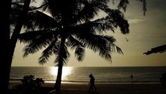 Two women walking on exotic tropical beach shore in Island at sunset Stock Footage