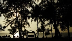 People lying and sitting on beach beds in tropical beach shore in island sunset Stock Footage
