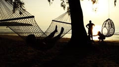 Couple playing with child and woman lying on hammock on tropical beach at sunset Stock Footage