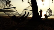 Stock Video Footage of Couple playing with child and woman lying on hammock on tropical beach at sunset