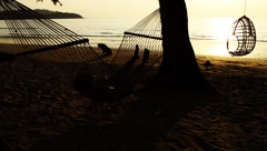 Woman lying on hammock and dog wandering around exotic tropical beach at sunset Stock Footage