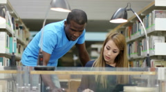 Two students reviewing homework in library at college - stock footage