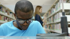 Young man studying in library at university Stock Footage