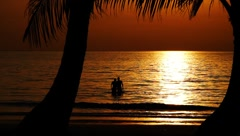 Healthy young couple in beautiful calm ocean on exotic tropical beach at sunset - stock footage