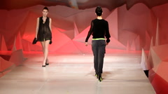 Fashion model walking on a runway with a red background Stock Footage