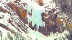 Colorized aqua Ice waterfalls Cascade down Evergreen forest Rocky mountain Slope Stock Footage