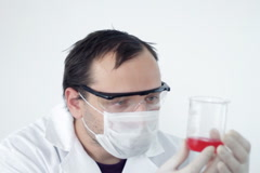 Male scientist examining beaker with red liquid NTSC Stock Footage