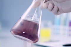 Scientist hand showing Erlenmeyer flask with violet substance NTSC Stock Footage