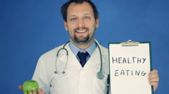 Male doctor showing apple and clipboard with HEALTHY EATING words on blue bg Stock Footage
