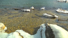 Icy Rocks and Boulders Shine on the Shore of Sunny Wintery Lake (colorized) Stock Footage