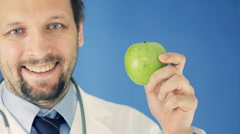 Male doctor showing apple and clipboard with HEALTHY EATING words, on blue bg Stock Footage