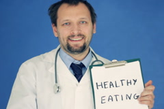 Male doctor writing HEALTHY EATING words on clipboard, on blue background NTSC Stock Footage