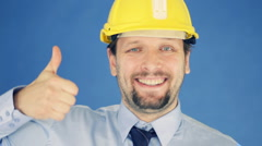 Successful engineer in yellow helmet showing ok sign, on blue background HD Stock Footage