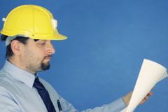 Construction engineer in yellow helmet looking at the project, on blue bg Stock Footage