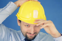 Construction engineer putting on yellow helmet, on blue background NTSC Stock Footage