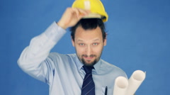 Construction engineer taking off yellow helmet, on blue background HD Stock Footage