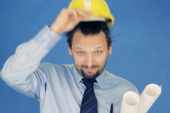 Construction engineer taking off yellow helmet, on blue background NTSC Stock Footage