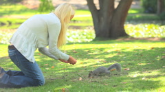 Young woman feeding a squirrel Stock Footage