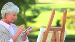 Mature woman painting Stock Footage