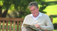 Mature man reading a newspaper on a bench Stock Footage