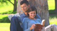 Young couple reading outdoors Stock Footage