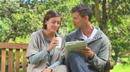Stock Video Footage of Young couple doing crosswords on a bench