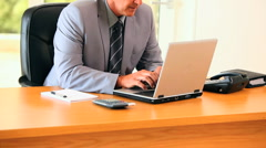 Grey-haired mature man working on his laptop - stock footage