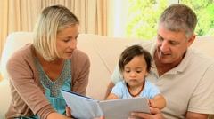Parents looking at book with baby Stock Footage