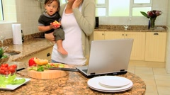 Young mother in kitchen coping with laptop phone and baby - stock footage