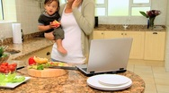 Stock Video Footage of Young mother in kitchen coping with laptop phone and baby
