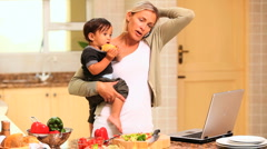 Woman in kitchen coping with baby and laptop and phone - stock footage