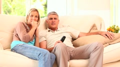 Couple on sofa enjoying an exciting TV programme - stock footage