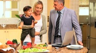 Couple in kitchen with baby and laptop Stock Footage