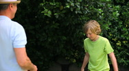 Father and son playing with a soccer ball in garden Stock Footage