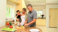 Couple with baby in kitchen preparing vegetables Stock Footage
