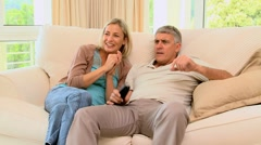 Couple on sofa delighted with programme on TV - stock footage