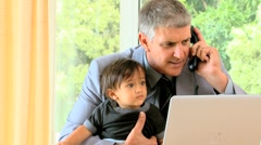 Man talking on phone while his baby is fidgeting on his lap Stock Footage