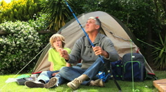 Man showing his child how to hang a worm on the hook Stock Footage