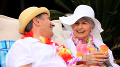 Senior couple laughing and sharing cocktails Stock Footage