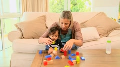 Stock Video Footage of Young mother playing with her baby with building blocks