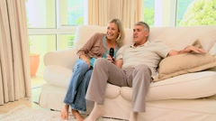 Couple on sofa ecstatic as they watch a programme on TV - stock footage