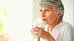 Mature woman sipping a glass of water Stock Footage